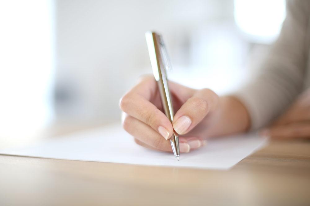 Frau schreib auf ein Blatt Papier
